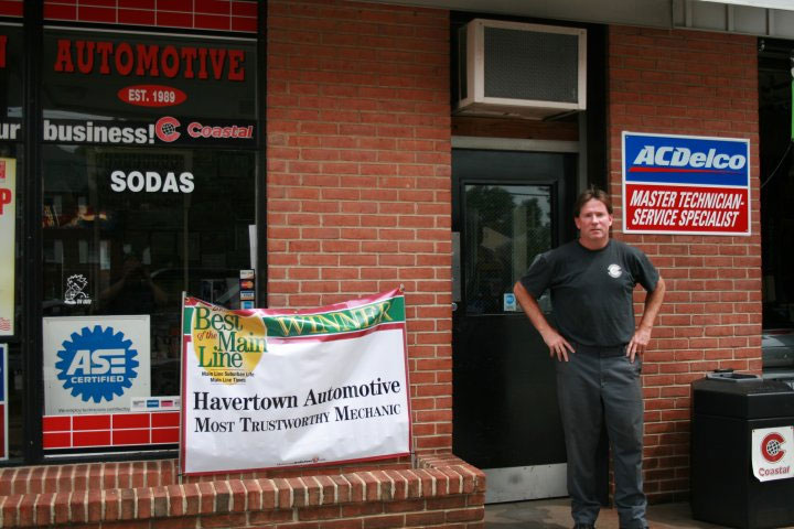 the owner outside his auto repair shop